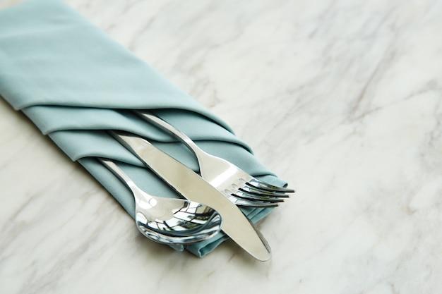Posate impostare un tovagliolo blu su marmo