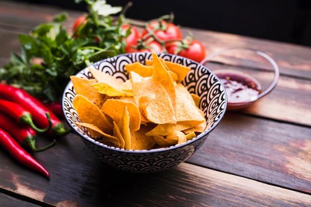 Posate piatte di nachos, verdure e ketchup