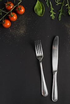 Posate vicino a pomodori e basilico