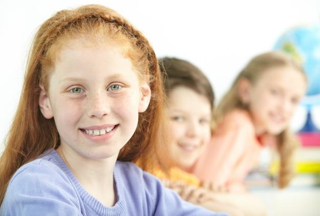 Positiva bambina con i compagni di classe sfondo