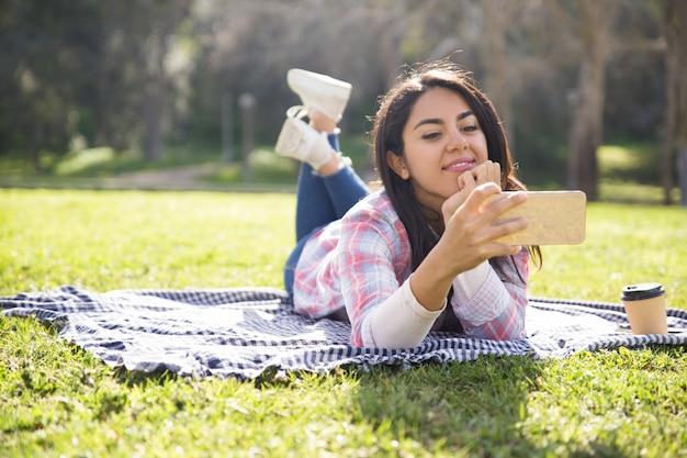 Positiva bella ragazza godendo perfetta connessione wireless