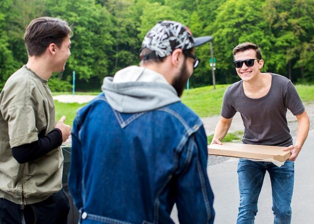 Positivi ragazzi giovani con la pizza nel parco