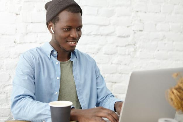 Positivo giovane ed elegante afroamericano copywriter in cappello indossando auricolari wireless in chat con il suo capo tramite videoconferenza su un computer portatile generico, guardando lo schermo e sorridendo allegramente