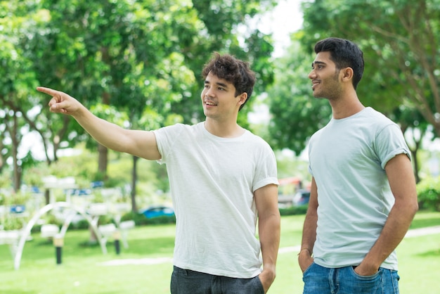 Positivo ragazzo amichevole che mostra la direzione per l'uomo indiano