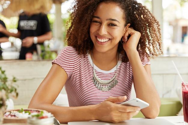 Positve donna afroamericana con aspetto allegro, felice di inviare messaggi con gli amici, utilizza un moderno telefono cellulare, si siede alla caffetteria, mangia deliziosi dessert e beve cocktail. tecnologia, concetto di riposo