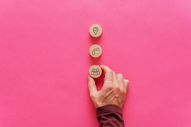 Posizionando tre cerchi di taglio in legno con icone di contatto e informazioni su di essi