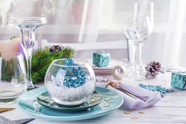 Posizionare la tavola per la tavola bianca di natale con elementi decorativi blu con rami di albero di natale verde