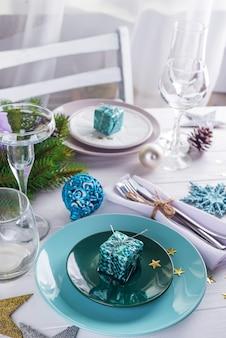 Posizionare la tavola per la tavola bianca di natale con elementi di decorazione viola con rami di albero di natale verde