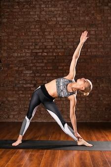 Posizione di ginnastica della donna della foto a figura intera