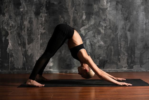 Posizione di yoga della donna della foto a figura intera sulla stuoia