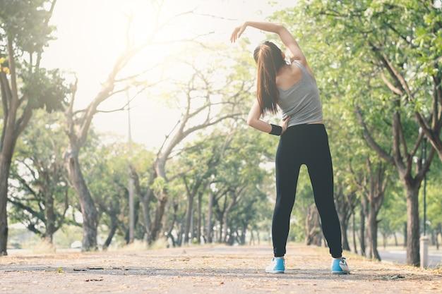 Posizione di yoga diritta della donna di forma fisica sulla via.