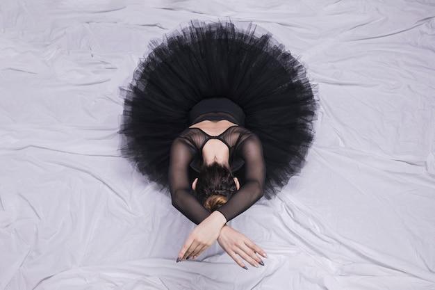 Posizione seduta della ballerina di vista frontale