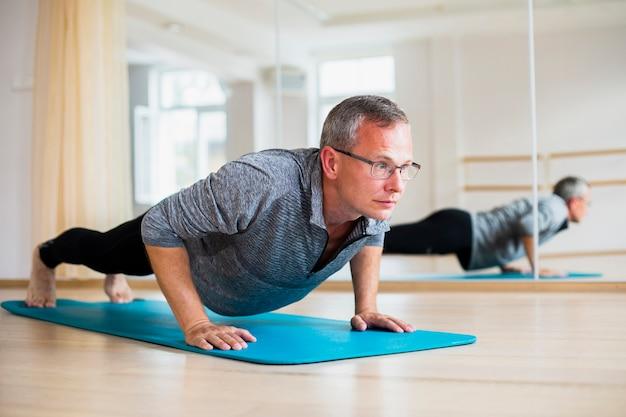 Posizioni di yoga di pratica dell'uomo adulto