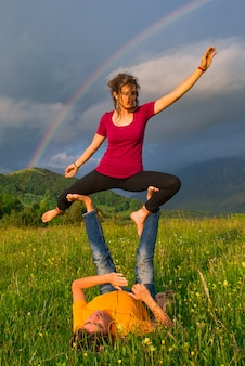 Posizioni di yoga in montagna con arcobaleno in background