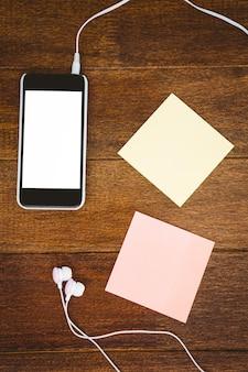 Post it e smartphone nero con cuffie bianche