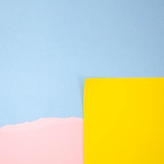Post-it giallo e rosa astratto con il fondo blu dello spazio della copia