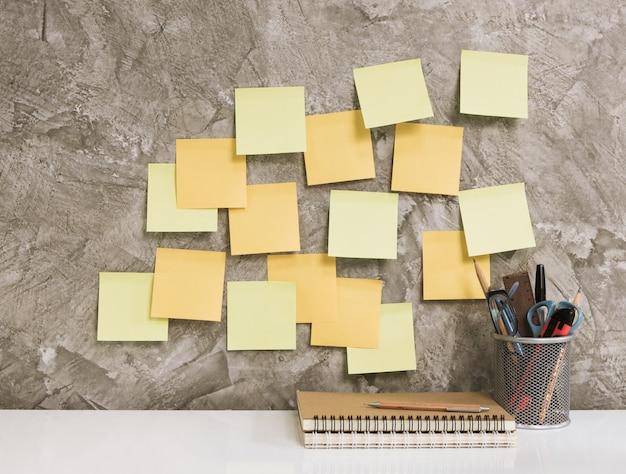 Post-it, taccuino, matita, occhiali da vista, penna, forbici e cactus sul fondo concreto del tavolo bianco, concetto di spazio di lavoro