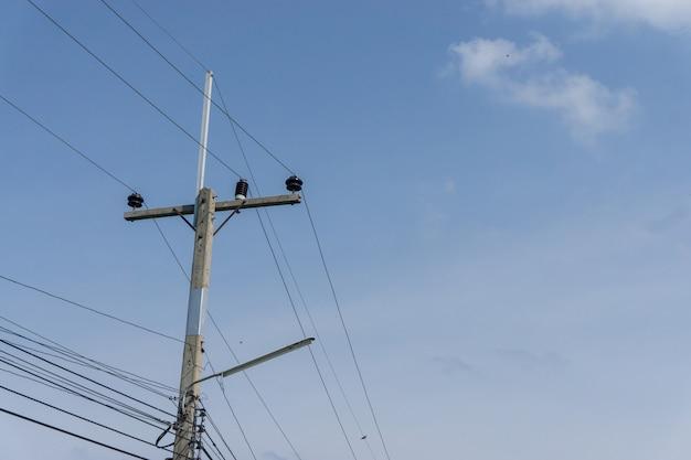 Posta di elettricità con il cielo blu della nuvola, copi lo spazio per testo