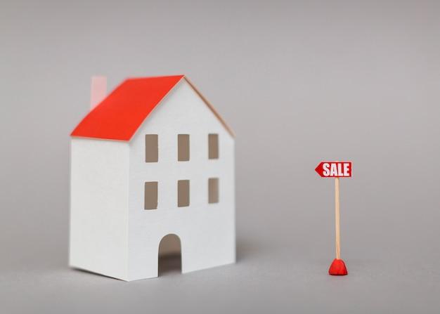 Posta di vendita vicino al modello di casa in miniatura su sfondo grigio