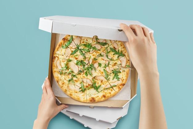 Poster concettuale per la consegna di cibo e pizza. pizza di carne in una scatola di cartone per la consegna su una superficie blu con posto per il testo. l'uomo apre una scatola di cibo