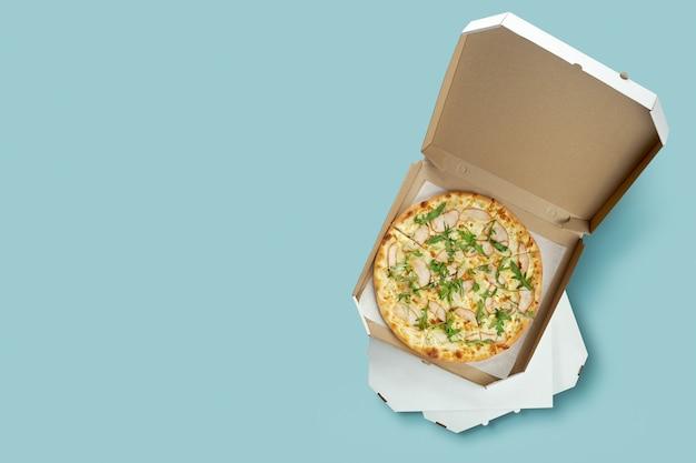 Poster concettuale per la consegna di cibo e pizza. pizza di carne in una scatola di cartone per la consegna su una superficie blu con posto per il testo