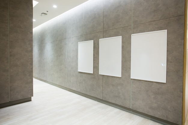 Poster quadrati vuoti sul muro di cemento nel corridoio vuoto