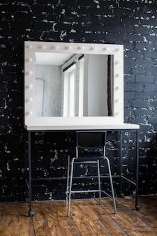 Posto del trucco della donna con lo specchio e le lampadine al muro di mattoni nero interno del sottotetto dello studio della foto