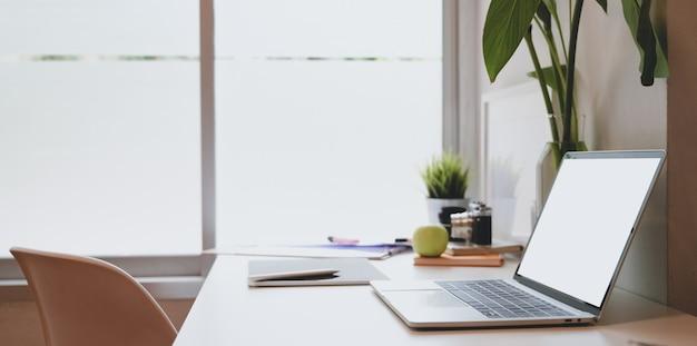 Posto di lavoro alla moda del fotografo con il computer portatile dello schermo in bianco