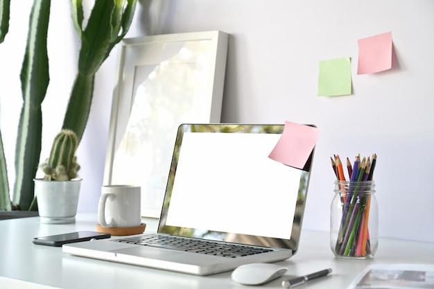 Posto di lavoro comodo in ufficio con il computer portatile dello schermo in bianco sulla tavola di legno bianca