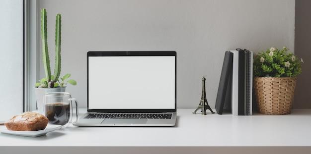 Posto di lavoro comodo vicino alle finestre con il computer portatile dello schermo in bianco aperto con la tazza di caffè
