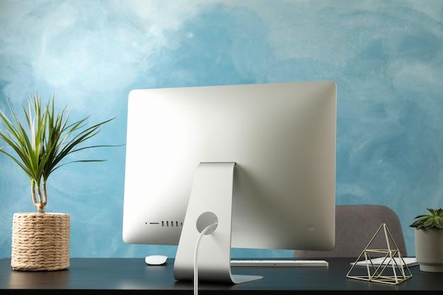 Posto di lavoro con computer e piante sul tavolo di legno nero e sedia, spazio per il testo