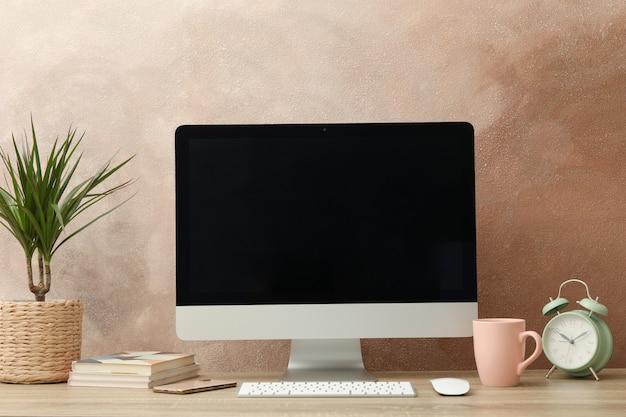 Posto di lavoro con computer, impianto e sveglia sul tavolo di legno.