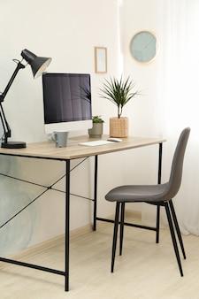 Posto di lavoro con computer, piante e lampada sul tavolo di legno. schermo nero vuoto