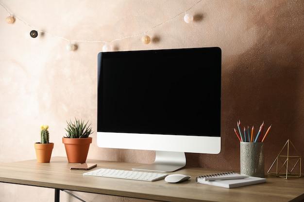 Posto di lavoro con computer, piante e taccuino sul tavolo di legno.