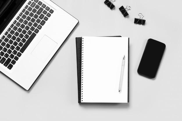 Posto di lavoro con computer portatile aperto, accessorio bianco e nero sul tavolo blu.
