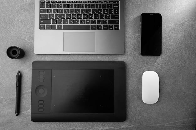Posto di lavoro con laptop aperto con schermo nero, mouse, tavoletta grafica e smartphone