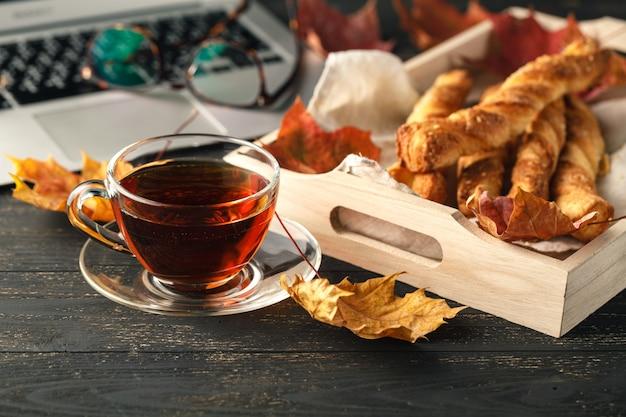 Posto di lavoro con laptop e biscotti dolci con una tazza di tè