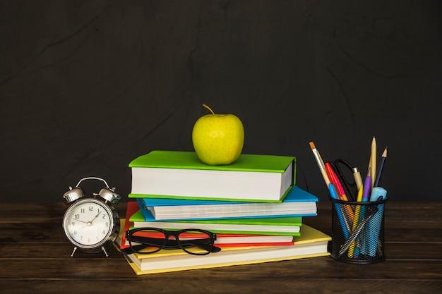 Posto di lavoro con libri occhiali sveglia e articoli di cancelleria