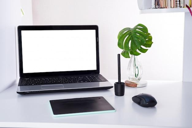 Posto di lavoro con notebook portatile e foglie di palma. tavolo da lavoro comodo in casa o in ufficio
