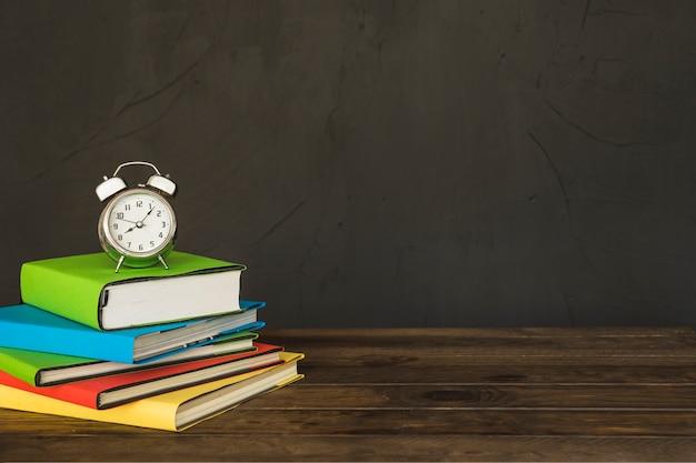Posto di lavoro con pile di libri e sveglie