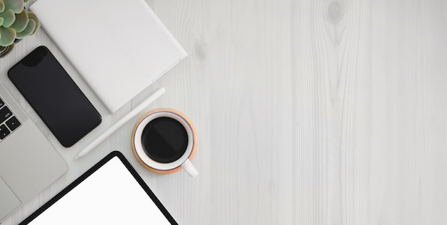 Posto di lavoro con tablet schermo vuoto, articoli per ufficio e copia spazio sul tavolo di legno bianco