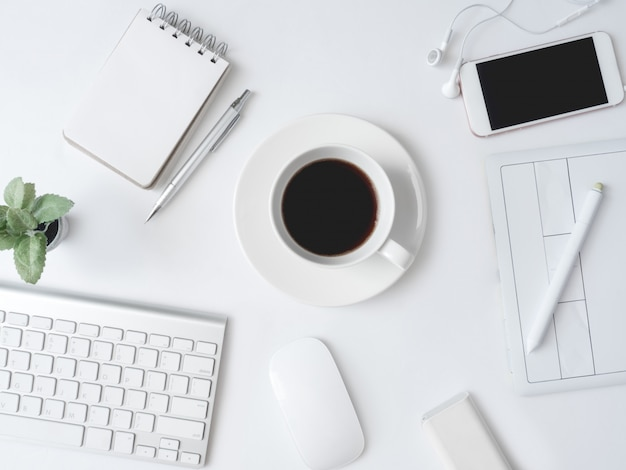 Posto di lavoro con tazza di caffè, taccuino, pianta di plastica, smartphone e tastiera sul tavolo