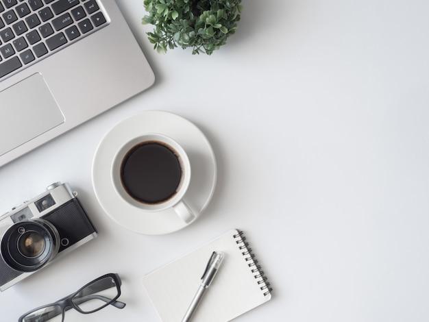 Posto di lavoro con tazza di caffè, taccuino, pianta in plastica e tastiera