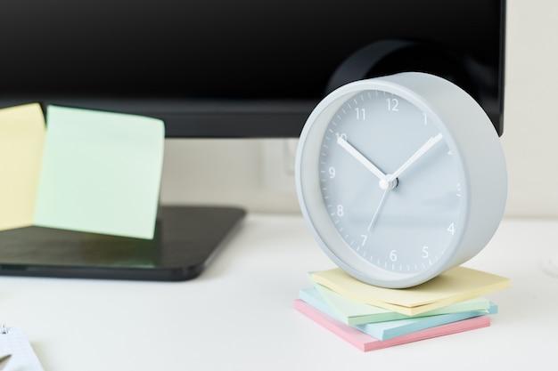 Posto di lavoro con un orologio, forniture per ufficio e bigliettini