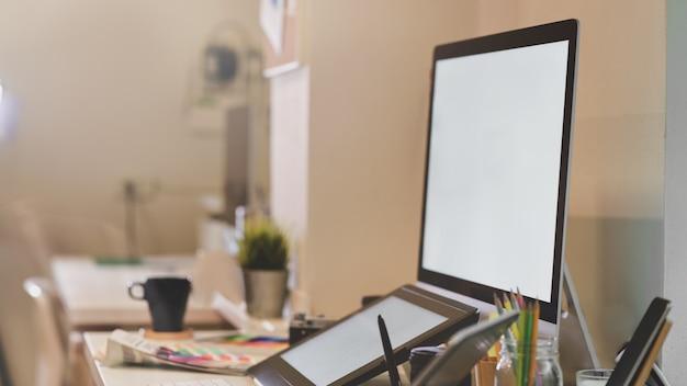 Posto di lavoro del fotografo con il desktop computer dello schermo in bianco