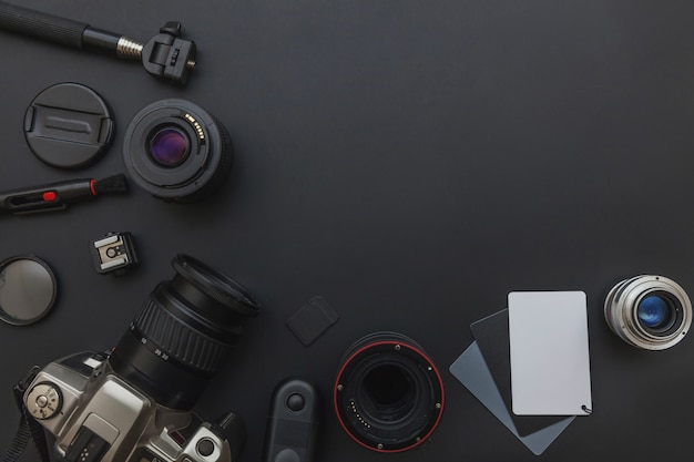 Posto di lavoro del fotografo con il sistema della macchina fotografica del dslr, il kit di pulizia della macchina fotografica, l'obiettivo e l'accessorio della macchina fotografica sul fondo della tavola del nero scuro