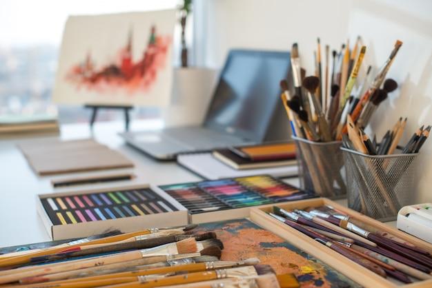 Posto di lavoro del pittore nell'ordine vista laterale. scrivania di design con attrezzatura da disegno. home studio per artista