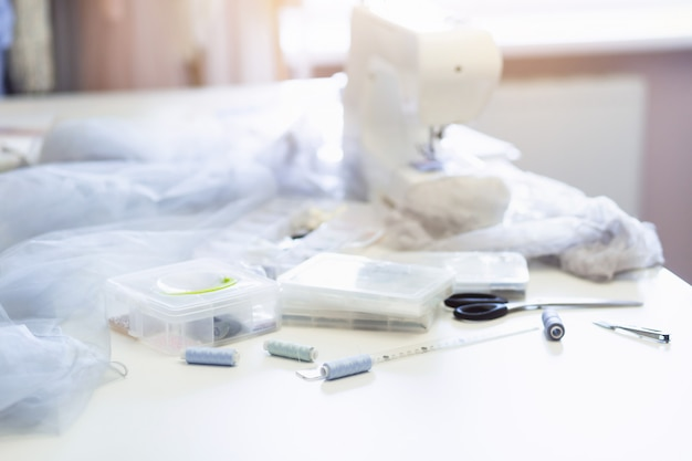 Posto di lavoro del sarto da donna o della sarta con la macchina per cucire, i fili e le forbici sulla tavola, fine su, fondo di luce solare