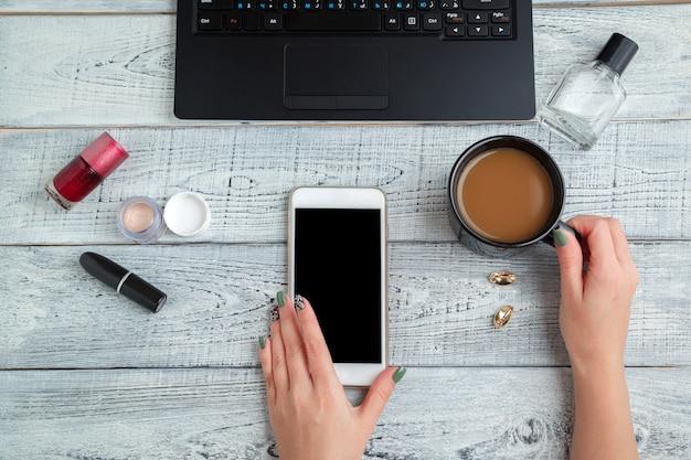 Posto di lavoro della donna con le mani delle donne, smartphone, laptop, tazza di caffè e cosmetici