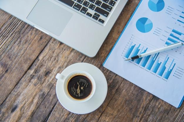 Posto di lavoro della scrivania con pc, grafici, smartphone e caffè sulla tavola di legno. vista dall'alto